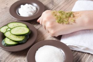 Applying cucumber, salt, and other natural exfoliants to back of hand
