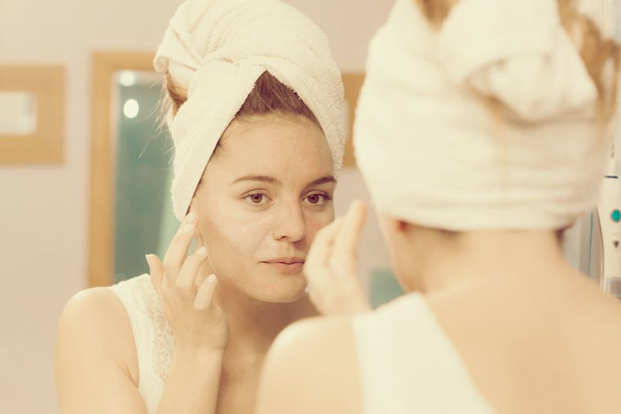 Young woman using mirror to apply exfoliating cream on face