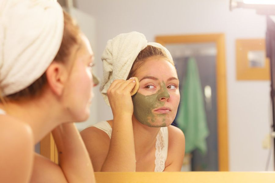 Woman wearing towel using face scrub and sponge to exfoliate in mirror